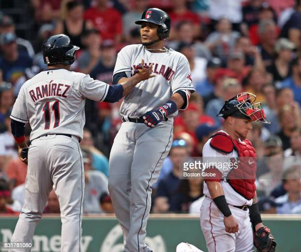 As the Indians' Edwin Encarnacion center crosses the plate after scoring teammate Jose Ramirez left with a top of the fifth inning tworun home run...