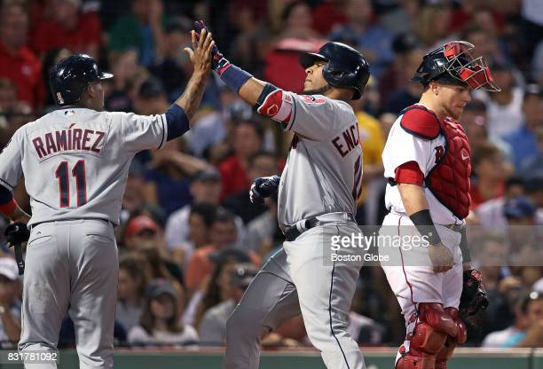 As the Indians' Edwin Encarnacion center crosses the plate after scoring teammate Jose Ramirez left with a top of the sixth inning tworun home run...