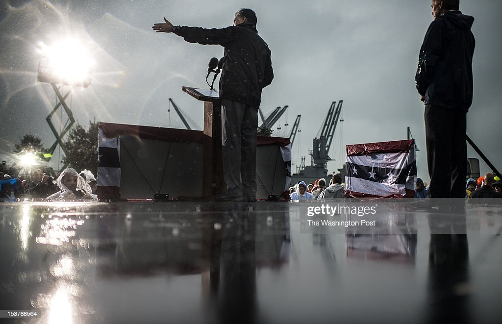 As the rain streams down, Republican nominee for President Governor Mitt Romney speaks to a supportive crowd, with Virginia Governor Bob McDonnell, right, at a rally on the docks in Newport News, Virginia, on Monday, October, 8, 2012.