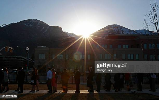 As the sun rises over the Wasatch Mountains a line of people wait outside the Provo City Center Temple of the Church of Jesus Christ of Latter Day...