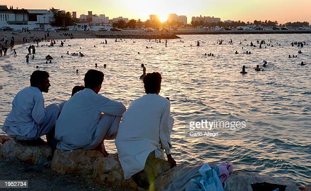 As the sun sets a group of men sit along the beach April 25 2003 in Doha Qatar As the USled war in Iraq winds down tensions amonst residents in the...