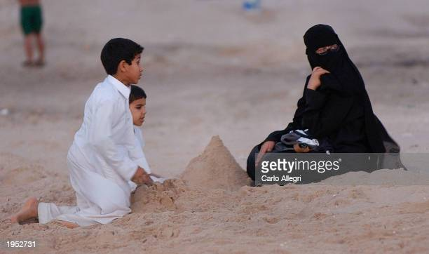 As the sun sets a woman and her children play on the beach April 25 2003 in Doha Qatar As the USled war in Iraq winds down tensions amonst residents...