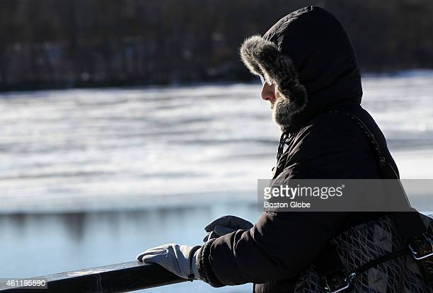 As the temperature hovers around zero degrees Jin Ling Wang of Lowell out for a walk with her husband stops to look out onto the icy surface of the...