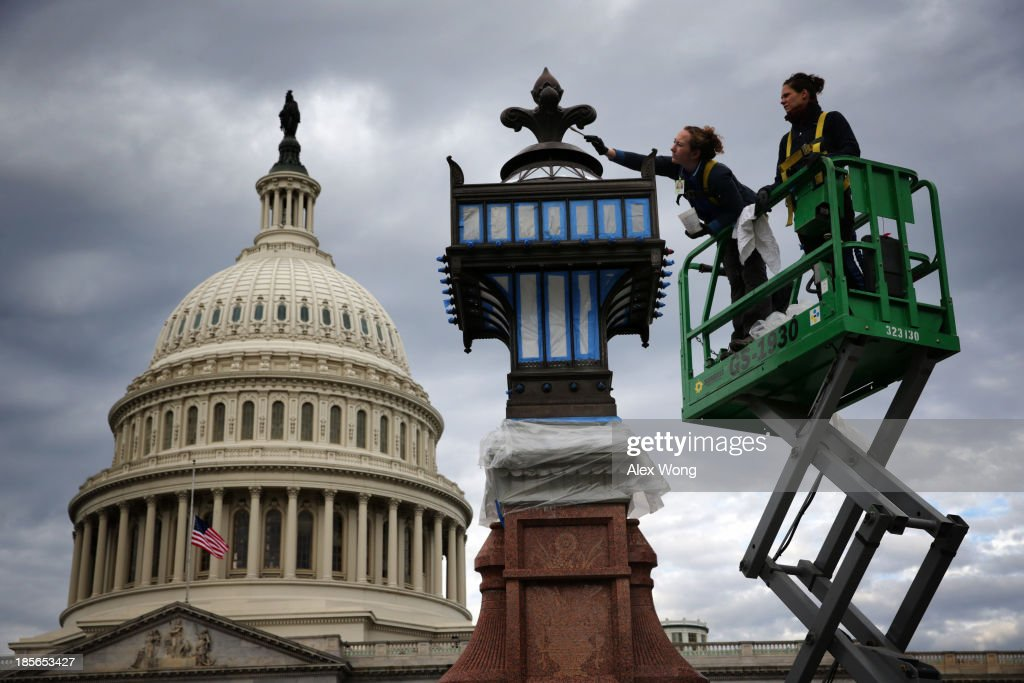 As the U.S. Capitol Dome is seen in the background, architectural conservators Caitlin Smith (L) and Lindy Gulick (R) clean the bronze frame of a light in front of the Capitol October 23, 2013 on Capitol Hill in Washington, DC. The Architect of the Capitol has announced yesterday that it will start a 2 year-long restoration project next month for the Capitol Dome which now has more than 1,000 cracks.