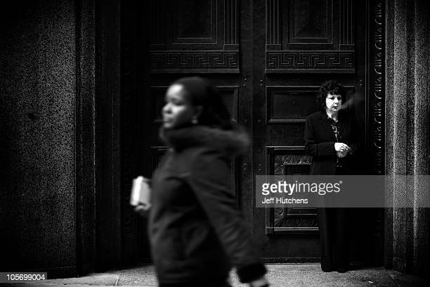 As the world economy struggles to overcome a recession a woman takes a smoke break outside the New York Stock Exchange in the heart of New York's...