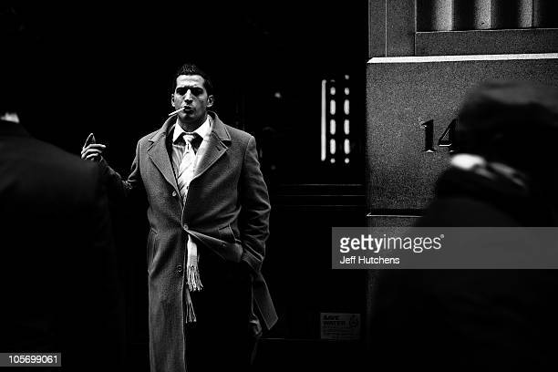 As the world economy struggles to overcome a recession men take a smoke break in the New York Stock Exchange area in the heart of New York's...