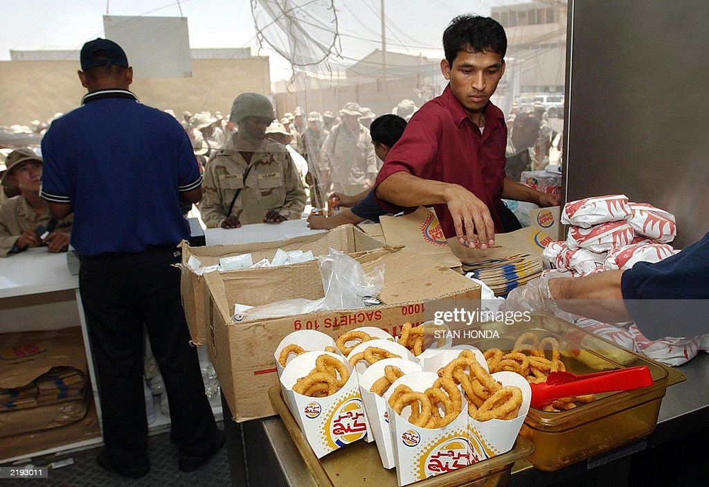 As US Army soldiers in background place their orders, workers prepare food at a Burger King take out restaurant in the army base set up at Saddam International Airport 14 July, 2003, in Baghdad. Coalition forces have renamed it Baghdad International Airport. If June saw a spike in ambush-style attacks against Americans, it also witnessed the army open its first Burger King and beef up the merchandise at its shopping centre to provide soldiers with the creature comforts of home. AFP PHOTO/Stan HONDA