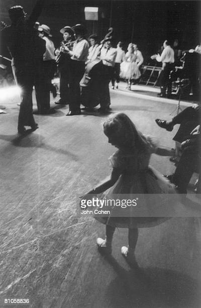 As various musicians rehearse in the background a young girl practices backstage at the Ryman Auditorium during a Grand Ol Opry performance Nashville...