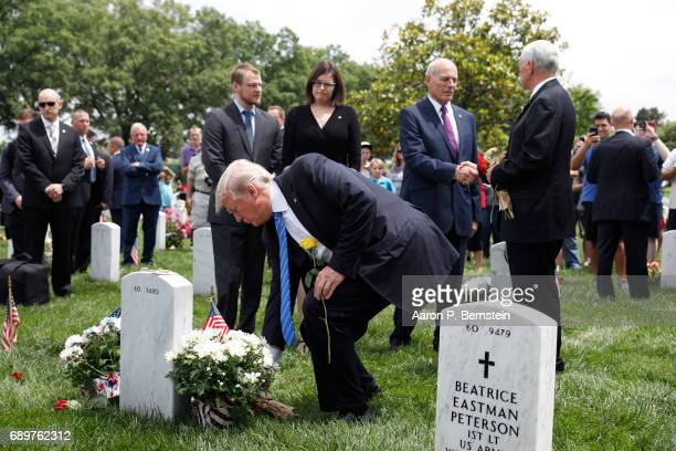 As Vice President Mike Pence and Secretary of Homeland Security John Kelly shake hands President Donald Trump lays flowers on the grave of Kelly's...