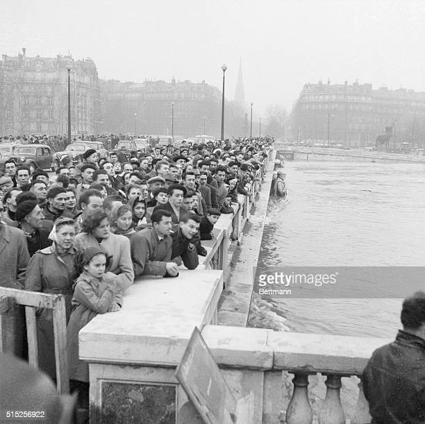 As water rises above the waist of the famed statue of the Zouave on the Alma Bridge Parisians watch with anxious fascination crowding the bridge like...