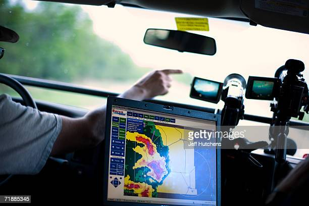 As weather monitoring computer equipment sits on the chase van's dashboard Kinney Adams Senior Chase Guide points out features in the clouds to storm...