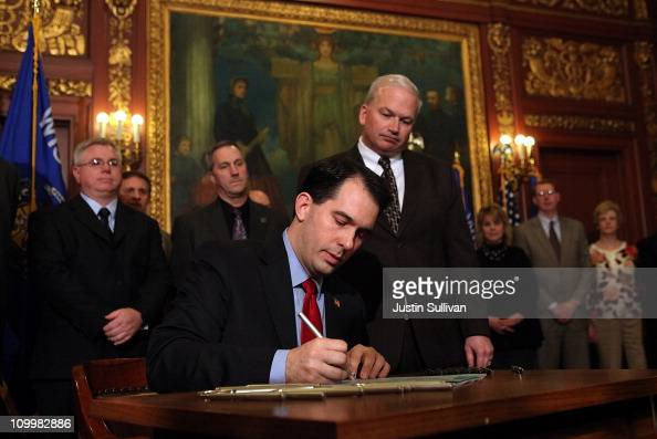 As Wisconsin Senate Majority Leader Scott Fitzgerald looks on Wisconsin Gov Scott Walker performs a ceremonial bill signing outside his office at the...