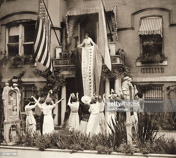 As women stand and cheer American suffragist Alice Paul stands on a balcony at the National Women's Party headquarters and unfurls a banner in...