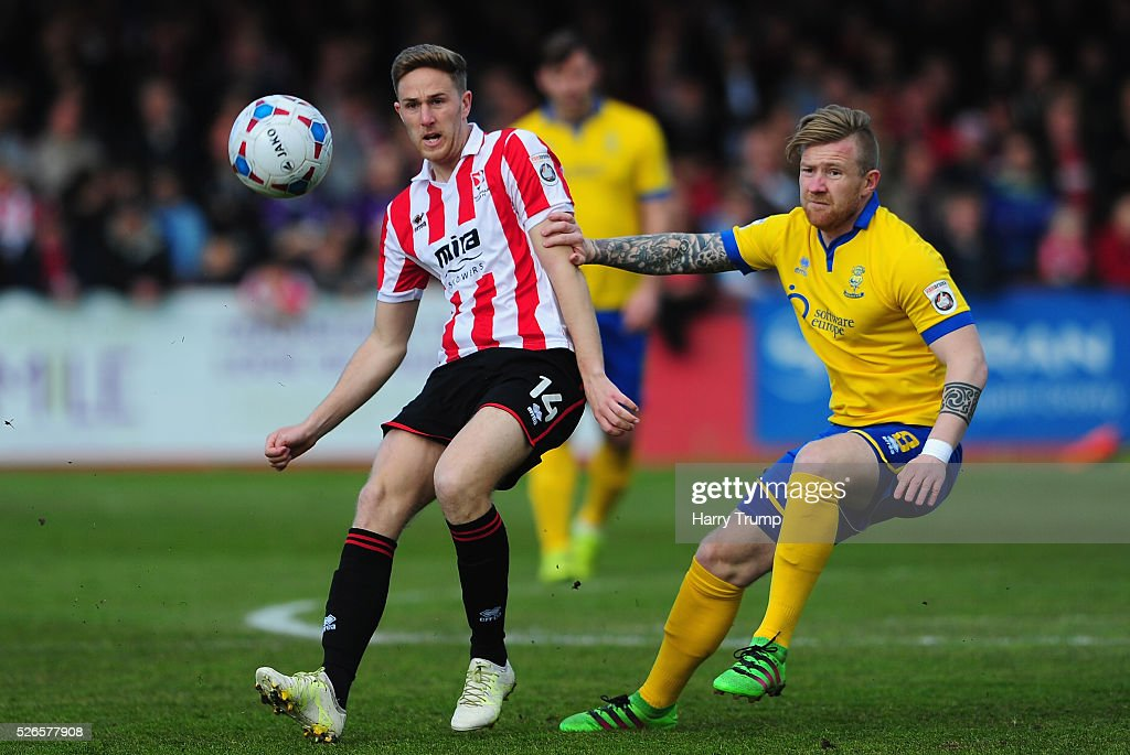 Asa Hall of Cheltenham Town is tackled by Alan Power of Lincoln City during the Vanarama Football Conference match between Cheltenham Town and Lincoln City at the World of Smile Stadium on April 30, 2016 in Cheltenham, England.