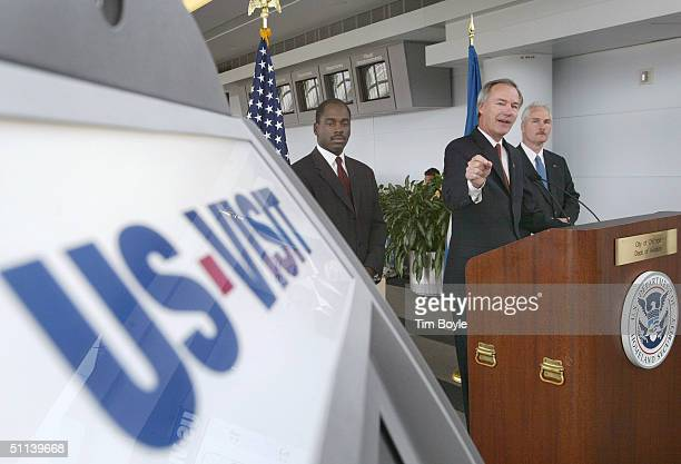 Asa Hutchinson UnderSecretary for Border and Transportation Security points towards a USVISIT kiosk at O'Hare International Airport August 3 2004 in...