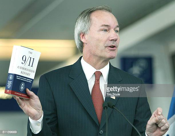 Asa Hutchinson UnderSecretary for Border and Transportation Security holds a copy of The 9/11 Commission Report during a demonstration of the USVISIT...