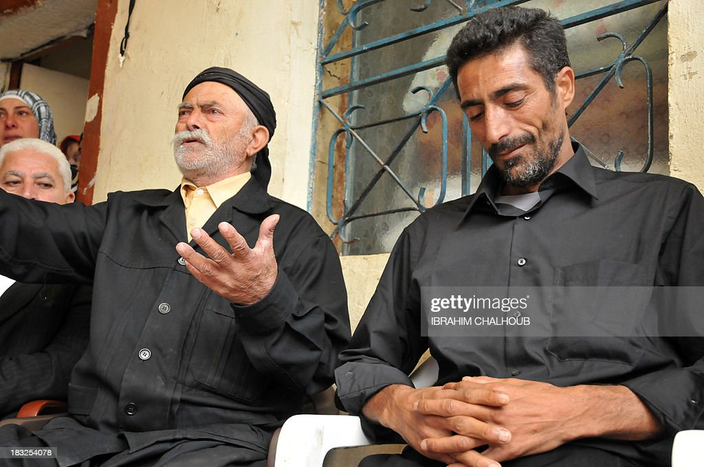 Asaad Asaad (R), a Lebanese survivor of the migrant shipwreck in Indonesia last week, sits next to his father as he arrives at their home on October 6, 2013 in Akkar, an impoverished and remote province of north Lebanon. The 18 survivors, who returned to Lebanon, expressed their anger against the Lebanese state that they accuse of disregarding their difficulties with the influx of Syrian refugees. Assaad lost his wife and their 3 children. AFP PHOTO IBRAHIM CHALHOUB