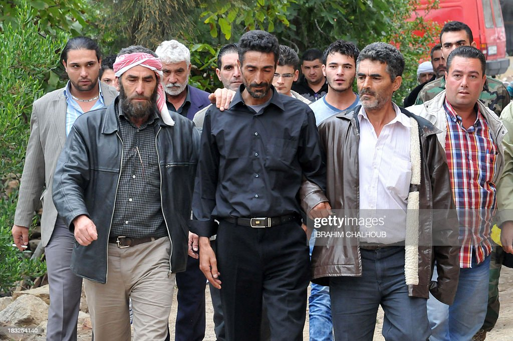 Asaad Asaad (C), a Lebanese survivor of the migrant shipwreck in Indonesia last week, is welcomed as he arrives at his family's home on October 6, 2013 in Akkar, an impoverished and remote province of north Lebanon. The 18 survivors, who returned to Lebanon, expressed their anger against the Lebanese state that they accuse of disregarding their difficulties with the influx of Syrian refugees. Assaad lost his wife and their 3 children.