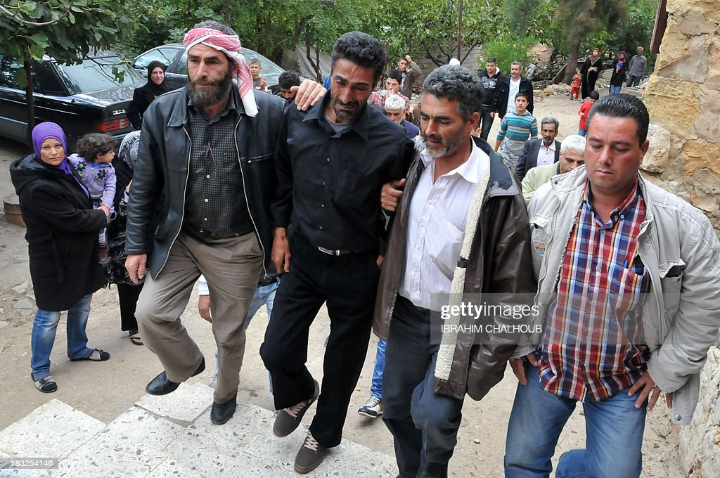 Asaad Asaad (C), a Lebanese survivor of the migrant shipwreck in Indonesia last week, is welcomed as he arrives at his family's home on October 6, 2013 in Akkar, an impoverished and remote province of north Lebanon. The 18 survivors, who returned to Lebanon, expressed their anger against the Lebanese state that they accuse of disregarding their difficulties with the influx of Syrian refugees. Assaad lost his wife and their 3 children. AFP PHOTO IBRAHIM CHALHOUB