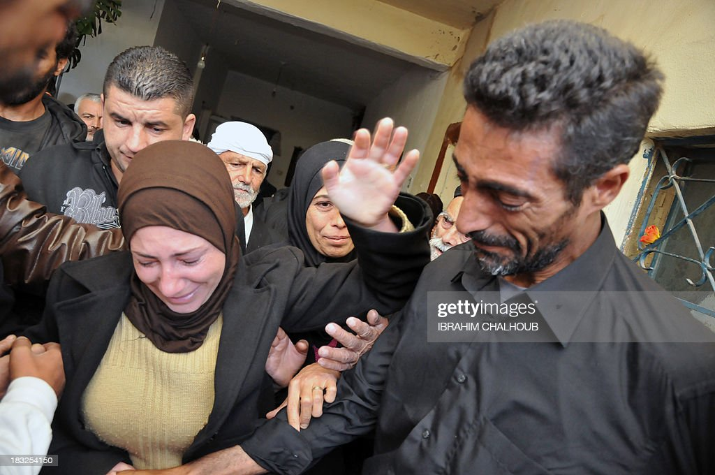 Asaad Asaad (R), a Lebanese survivor of the migrant shipwreck in Indonesia last week, is welcomed by relatives as he arrives at their home on October 6, 2013 in Akkar, an impoverished and remote province of north Lebanon. The 18 survivors, who returned to Lebanon, expressed their anger against the Lebanese state that they accuse of disregarding their difficulties with the influx of Syrian refugees. Assaad lost his wife and their 3 children.