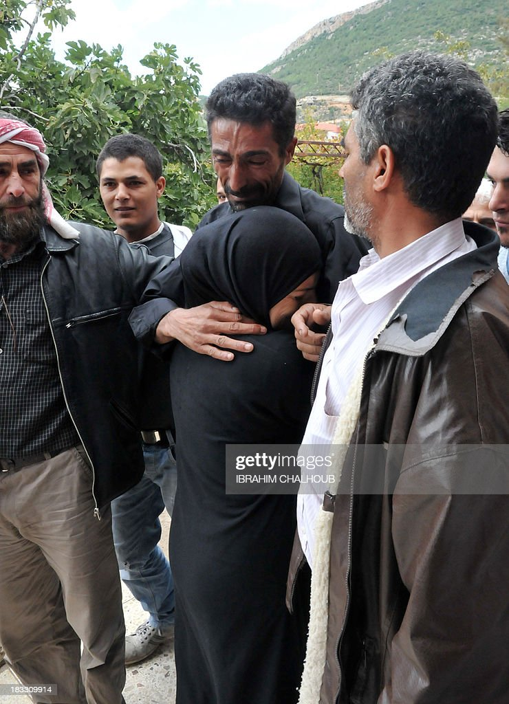 Asaad Asaad (C), a Lebanese survivor of the migrant shipwreck in Indonesia last week, is welcomed by relatives as he arrives at their home on October 6, 2013 in Akkar, an impoverished and remote province of north Lebanon. The 18 survivors, who returned to Lebanon, expressed their anger against the Lebanese state that they accuse of disregarding their difficulties with the influx of Syrian refugees. Assaad lost his wife and their 3 children. AFP PHOTO IBRAHIM CHALHOUB