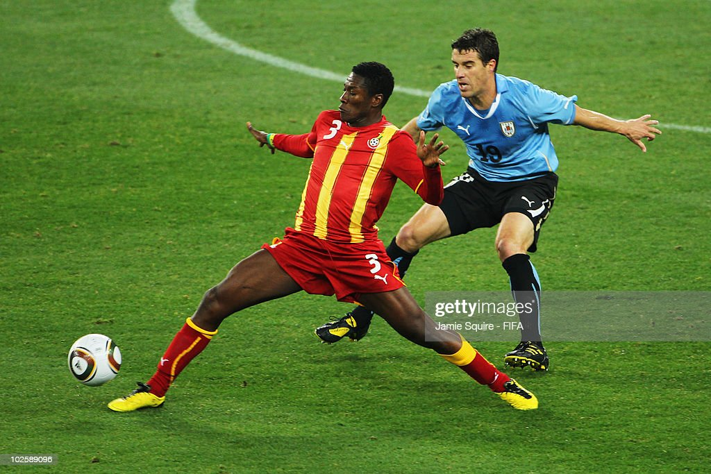 Asamoah Gyan of Ghana attempts to control the ball as he is closed down by Andres Scotti of Uruguay during the 2010 FIFA World Cup South Africa...