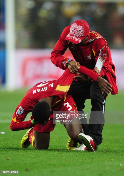Asamoah Gyan of Ghana is consoled after his team are knocked out in a penalty shoot out during the 2010 FIFA World Cup South Africa Quarter Final...