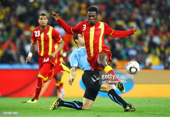 Asamoah Gyan of Ghana is tackled by Andres Scotti of Uruguay during the 2010 FIFA World Cup South Africa Quarter Final match between Uruguay and...
