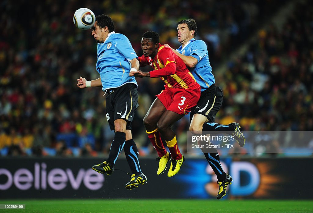 Asamoah Gyan of Ghana jumps between Mauricio Victorino and Andres Scotti of Uruguay during the 2010 FIFA World Cup South Africa Quarter Final match...
