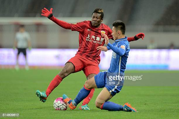 Asamoah Gyan of Shanghai SIPG competes for the ball with Li Yunqiu of Shanghai Shenhua during their Chinese Super League football match in Shanghai...