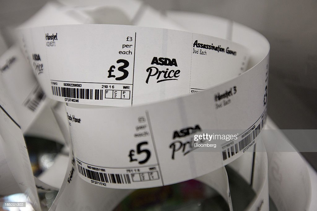 Asda 'Price' logos sit on a roll of labels for entertainment DVD goods inside an Asda supermarket, the U.K. retail arm of Wal-Mart Stores Inc., in Watford, U.K., on Thursday, Oct. 17, 2013. U.K. retail sales rose more than economists forecast in September as an increase in furniture demand led a rebound from a slump the previous month. Photographer: Simon Dawson/Bloomberg via Getty Images