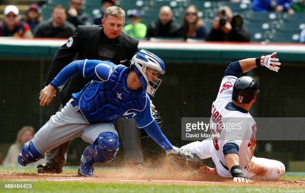 Asdrubal Cabrera of the Cleveland Indians attempts to score ahead of the tag by Brett Hayes of the Kansas City Royals as home plate umpire Greg...