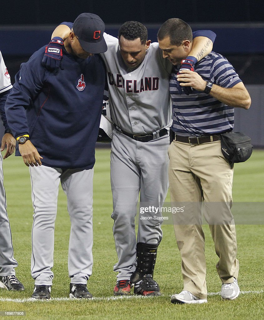 <a gi-track='captionPersonalityLinkClicked' href=/galleries/search?phrase=Asdrubal+Cabrera&family=editorial&specificpeople=834042 ng-click='$event.stopPropagation()'>Asdrubal Cabrera</a> #13 of the Cleveland Indians is helped off the field by manager <a gi-track='captionPersonalityLinkClicked' href=/galleries/search?phrase=Terry+Francona&family=editorial&specificpeople=171936 ng-click='$event.stopPropagation()'>Terry Francona</a> #17 of the Cleveland Indians and a team trainer after he hurt himself while running to first base against the New York Yankees in the fifth inning at Yankees Stadium on June 3, 2013 in the Bronx borough of New York City. (Photo by Jason Szenes/Getty Images
