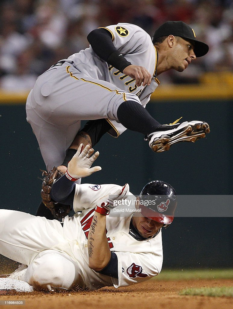 Asdrubal Cabrera of the Cleveland Indians steals second base underneath Ronny Cedeno of the Pittsburgh Pirates during the seventh inning of their...
