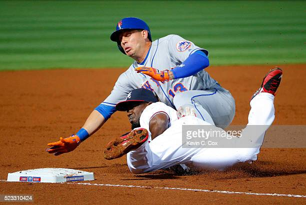 Asdrubal Cabrera of the New York Mets slides safely onto third base over top of Adonis Garcia of the Atlanta Braves on a throwing error by Bud Norris...