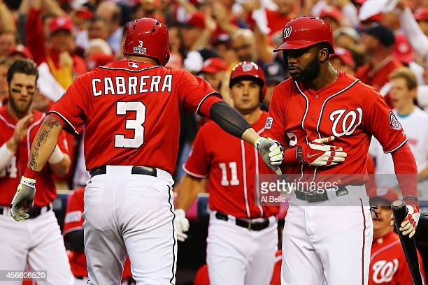 Asdrubal Cabrera of the Washington Nationals celebrates his in the seventh inning home run with teammates during Game One of the National League...