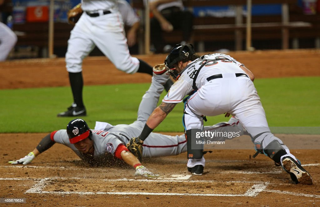Asdrubal Cabrera of the Washington Nationals scores as Jarrod Saltalamacchia of the Miami Marlins applies the tag during a game at Marlins Park on...