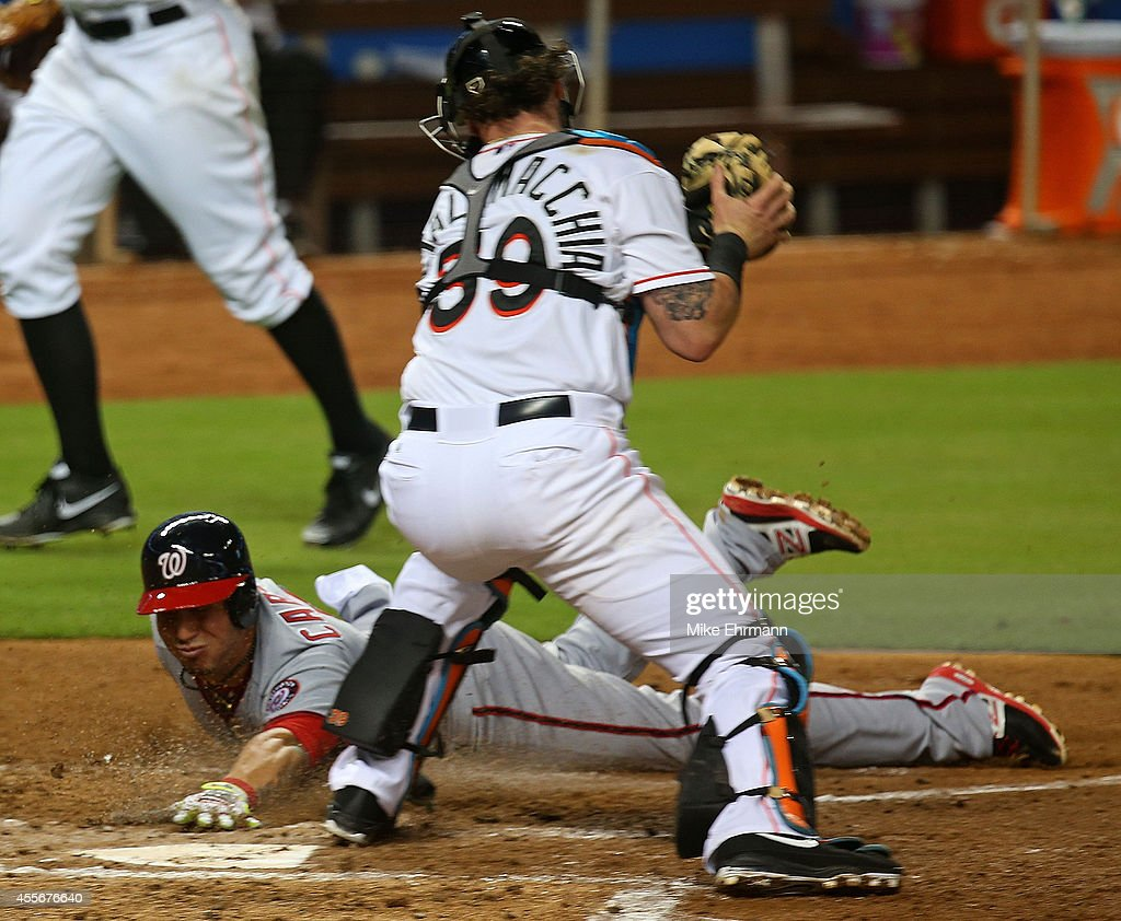 Asdrubal Cabrera #3 of the Washington Nationals scores as Jarrod Saltalamacchia #39 of the Miami Marlins applies the tag during a game at Marlins Park on September 18, 2014 in Miami, Florida.