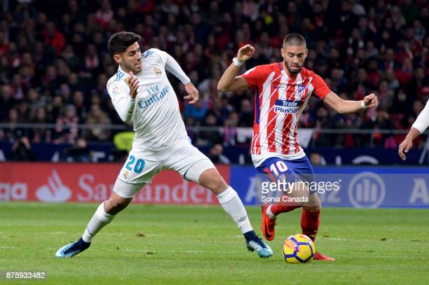 Asensio #20 of Real Madrid and Yannick #10 of Atletico de Madrid during The La Liga match between Club Atletico Madrid v Real Madrid at Wanda...