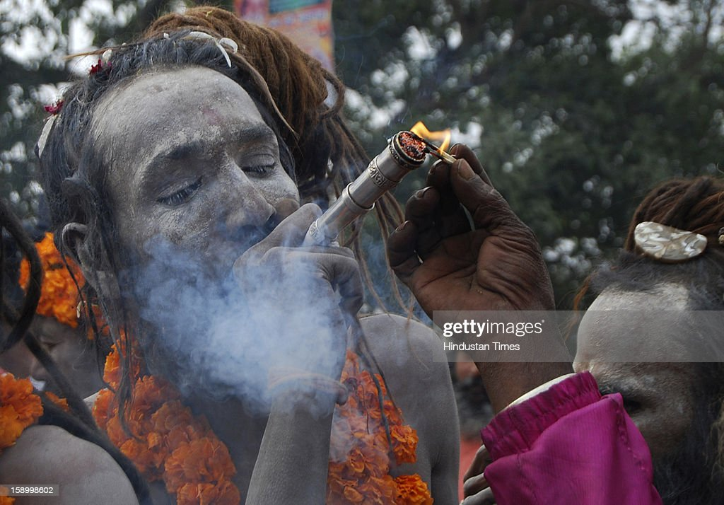 A ash smeared Naga sadhu smoking marijuana in the traditional 'Chillum' during Peshwai Juloos (procession)of Atal Akhada at the Sangam, confluence of the Rivers Ganges, Yamuna and mythical Saraswati on January 5, 2013 in Allahabad, India. Naga Sadhus belong to the Shaiva sect and consider consumption of Marijuana as sacred ritual which will lead to Nirvana, meaning final emancipation of the soul. The Kumbh Mela is mass Hindu pilgrimage that alternates between four places Allahabad, Haridwar, Ujjain and Nashik every three years. The current Kumbh is scheduled to take place at Allahabad city in January and February 2013 and is expected to be attended by 60 million devotees