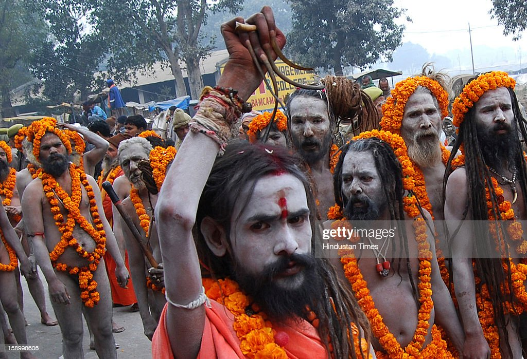 Ash smeared Naga Sadhu (Hath Yogi) with his raised hand and over grown nails during Royal Peshwai Juloos (procession)of Atal Akhada at the Sangam, confluence of the Rivers Ganges, Yamuna and mythical Saraswati on January 5, 2013 in Allahabad, India. Many Naga Sanyasis don't wear any cloth on their body. The Kumbh Mela is mass Hindu pilgrimage that alternates between four places Allahabad, Haridwar, Ujjain and Nashik every three years. The current Kumbh is scheduled to take place at Allahabad city in January and February 2013 and is expected to be attended by 60 million devotees