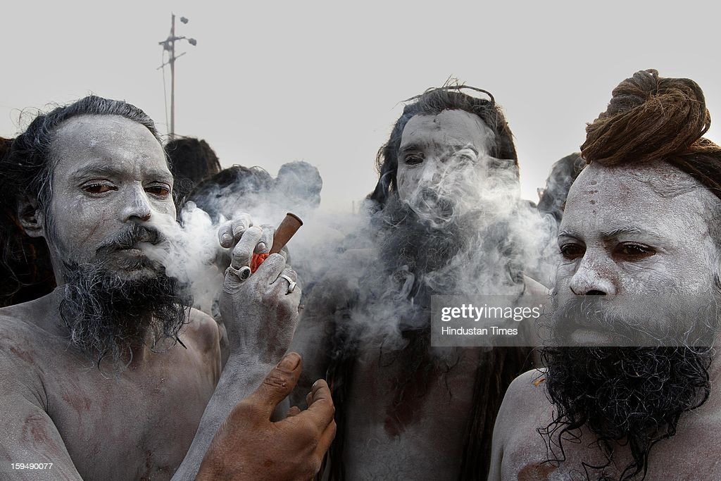 Ash smeared Naga Sadhus smoking through chillums before taking Shahi Snan (royal bath) at the bank of Sangam confluence of river Ganga, Yamnuna and mythical Saraswati on the occasion of Makar Sankranti on January 14, 2013 in Allahabad, India. Kumbh is World's biggest religious gathering, in which more that 100 million of Hindus and sikh devotees will take part over next 55 days. Apart from being pilgrimage of faith, salvation and hope for millions of devotees, it also serve as meeting ground for the vast spectrum of Indian religious and spiritual views.