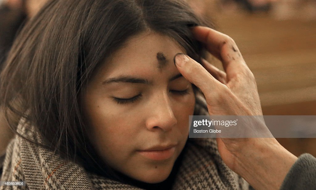 Ash Wednesday at Saint Anthony Shrine in Boston, Maria Rincon from Boston gets a cross of ashes applied to her forehead.