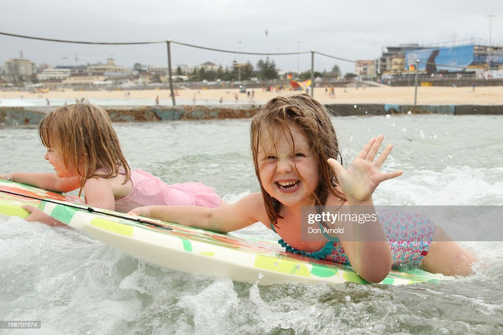 Asha and Evie Roe enjoy riding their boogie boards in the wading pool at Bondi Beach on December 25, 2012 in Sydney, Australia. Traditionally beaches such as Bondi Beach are popular destinations for tourists and locals alike to celebrate Christmas Day.