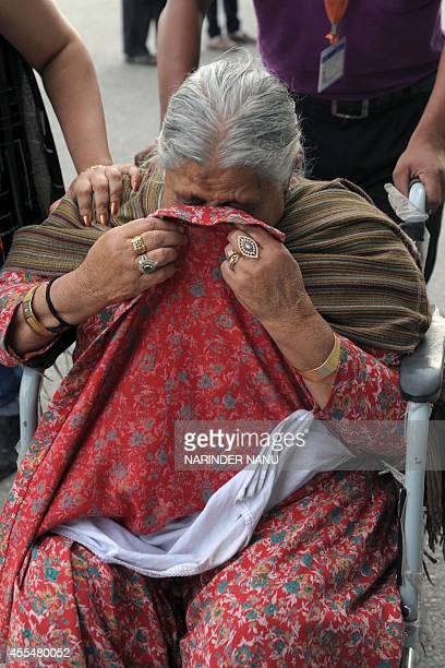 Asha Rani an Indian Sikh evacuated from flooding in Srinagar cries following her arrival at the airport in Amritsar on September 15 2014 Some 88...
