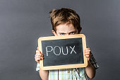 ashamed preschool child with unhappy blue eyes holding a protecting school slate with 'poux' written in French on it for head lice terror, grey background studio