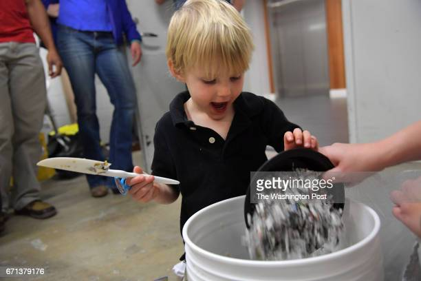 Asher Brownlie helps his mother add shredded newspaper to the blended mix of coffee grounds apples banana peels egg shells and other fruits and...