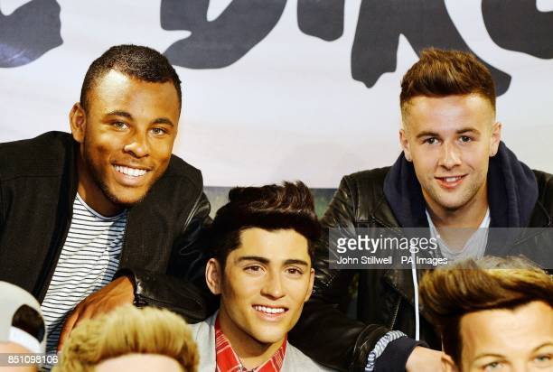 Ashford Campbell and Andy Merry members of the XFactor TV show contestants The Risk boyband pose with former contestant the wax model of Zayn Malik...