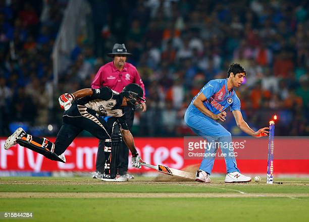 Ashish Nehra of India runs out Grant Elliott of New Zealand during the ICC World Twenty20 India 2016 Group 2 match between New Zealand and India at...