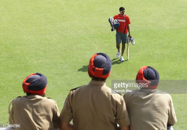 Ashish Nehra walks across the field while being watched by three policemen during an India nets session at the Punjab Cricket Association Stadium on...